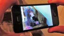 A mobile phone looking at an augmented image of a puppet in a New York subway station