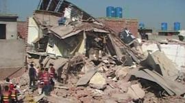 Rescuers search through the collapsed factory in Lahore