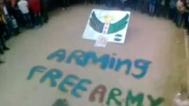 Crowd stand around words saying 'ARMING FREE ARMY'