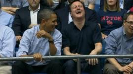 Barack Obama and David Cameron share a joke while watching the basketball game.