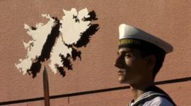 Argentine sailor in front of map of Falkland Islands