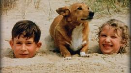 Prince Charles and Princess Anne as children buried in sand on beach with dog