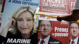 A supporter of Front National leader Marine Le Pen pastes one of her posters next to one of far left Front de Gauch leader Jean-Luc Melenchon