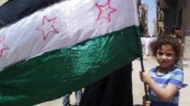 A girl holding the Syrian revolutionary flag