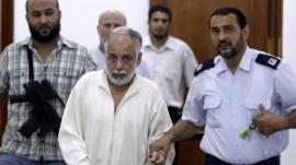 Libya's former Prime Minister al-Baghdadi al-Mahmoudi (centre) under escort