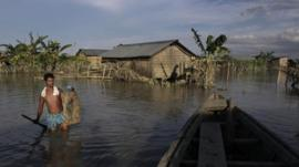 An Indian villager wades through flood waters at Gagalmari village in Assam state