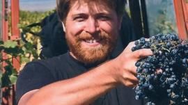 John Wurdeman holding grapes