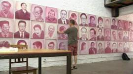 Beijing artist Zhang Bingjian hanging a portrait of a corrupt official in his 'Hall of Fame'