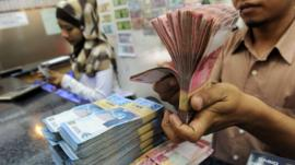 Bank teller with Indonesian rupiah notes