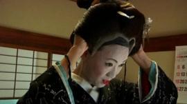 Geisha trainee puts finishing touches to her costume