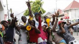 Jamaicans celebrate after Bolt and Blake won in the mens 200m final during the London 2012 Olympic Games at Half Way Tree in Kingston
