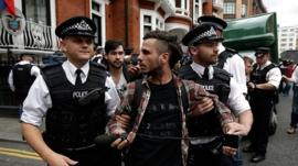 Police detain a supporter of Julian Assange, the founder of the WikiLeaks website, for obstructing the highway outside the Ecuadorean Embassy