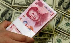 Chinese yuan currency and US dollar bills