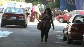 A woman walks down a street in Cairo