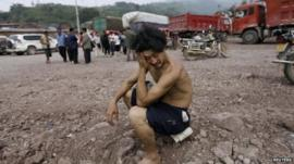Man sits surrounded by rubble