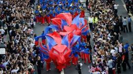 Performers dressed as red and blue lions pass along Fleet Street during the London 2012 Victory Parade for Team GB and Paralympic GB athletes