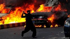 A Pakistani demonstrator brandishes a stick near burning police vehicles