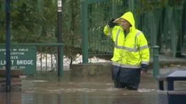 Man walks through flood water in Morpeth