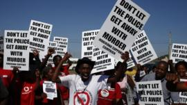 Demonstrators wave placards during a site inspection by the judicial commission