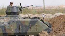 A Turkish soldier stands guard in an armoured personnel carrier on the Turkish-Syrian border near the Akcakale border crossing on 05 Oct 2012