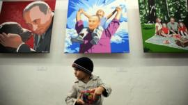 Small boy in front of Putin paintings