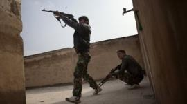 Rebel fighters fire from the roof-top of house against in the Bab el-Adid district in Aleppo on October 23