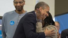 President Barack Obama is embraced by a volunteer as he visits a campaign office the morning of the 2012 electio