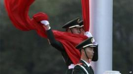 Chinese policeman holding flag in Tiananmen Square