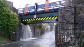 Water cascading off railway line onto the road below