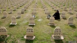 A woman visits the graves of relatives who were killed in a gas attack by former Iraqi president Saddam Hussein in 1988.