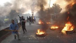 Activists of Bangladesh's Jamaat-e-Islami party set fire to tyres as they block a street in Narayanganj