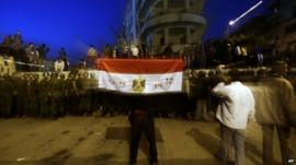 Protester with Egyptian flag near line of security forces
