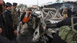 A damaged car in a bomb attack at Fauji Market in Peshawar