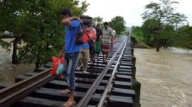 Sri Lankans walk on a rail road bridge across rising floodwaters