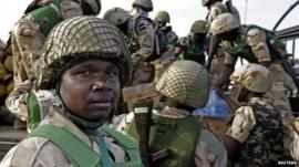 Nigerian soldiers unload their equipment as they arrive at the Mali air force base