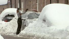 Woman scraping snow from car