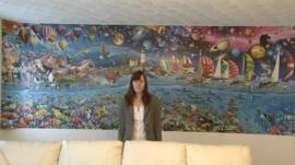 Amanda Warrington from South Gloucestershire, standing in front of her completed 24,000 jigsaw puzzle