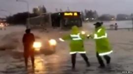 Car emerging from foam with two people with florescent jackets in front