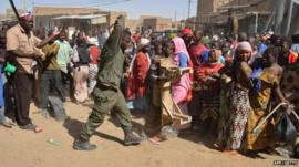 A Malian soldiers tries to disperse the crowd on January 29, 2013 in Timbuktu as residents plunder stores they say belong to Arabs, Mauritanians and Algerians
