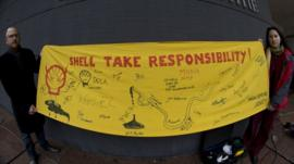 Friends of the Earth campaigners holding a banner demanding Shell take responsibility for the leaks in Nigeria