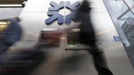A pedestrian walks past a branch of the Royal Bank of Scotland in the City of London