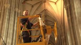 Man on cherry picker in cathedral
