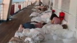 Still from amateur footage shows people sleeping on the deck of the Carnival Triumph