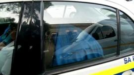 Oscar Pistorius hiding under a blanket in a police car