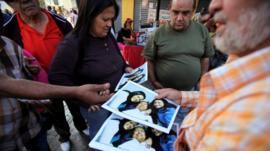 A man sells Chavez prints at 20 bolivars each
