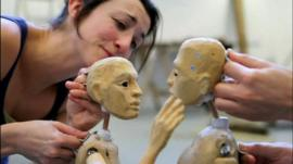 Actors rehearse with two wooden puppets