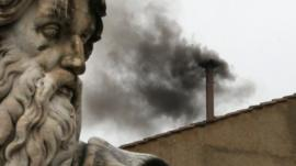 Black smoke billows from the chimney on the roof of the Sistine Chapel