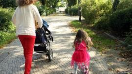 Mother and her three-year-old daughter walk together