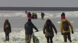 People watching emergency teams heading out to rescue those stranded on the ice floes