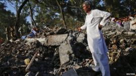 A man stands on the rubble of a collapsed building in the Thane district, near Mumbai